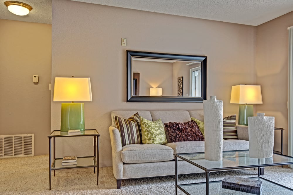 Carpeted living room with decorative mirror and furniture at The Lakes of Schaumburg in Schaumburg, Illinois
