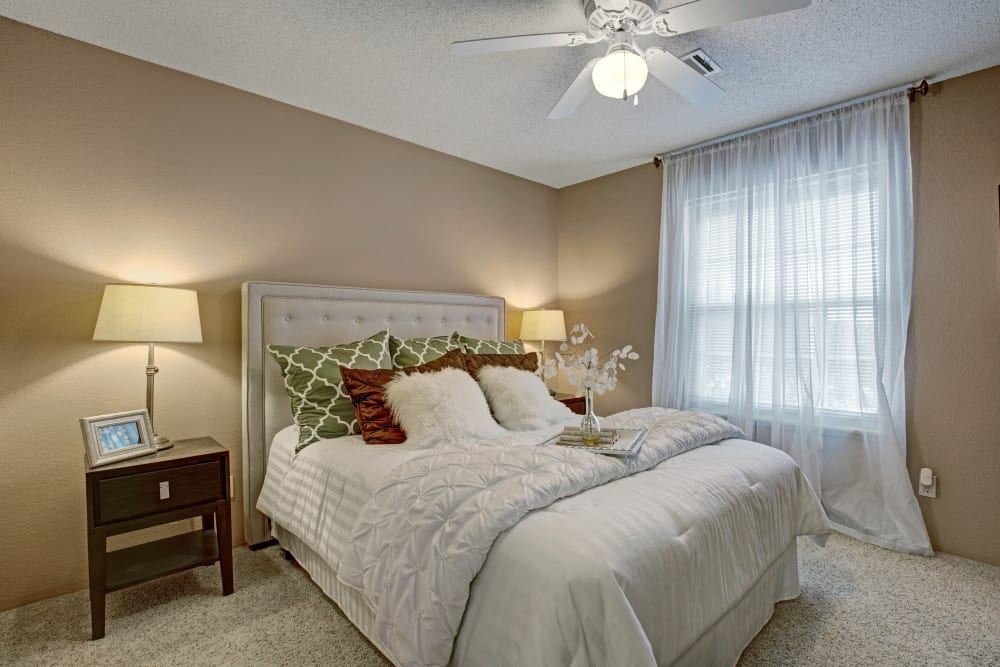 Well lit model bedroom with the ceiling fan at The Lakes of Schaumburg in Schaumburg, Illinois