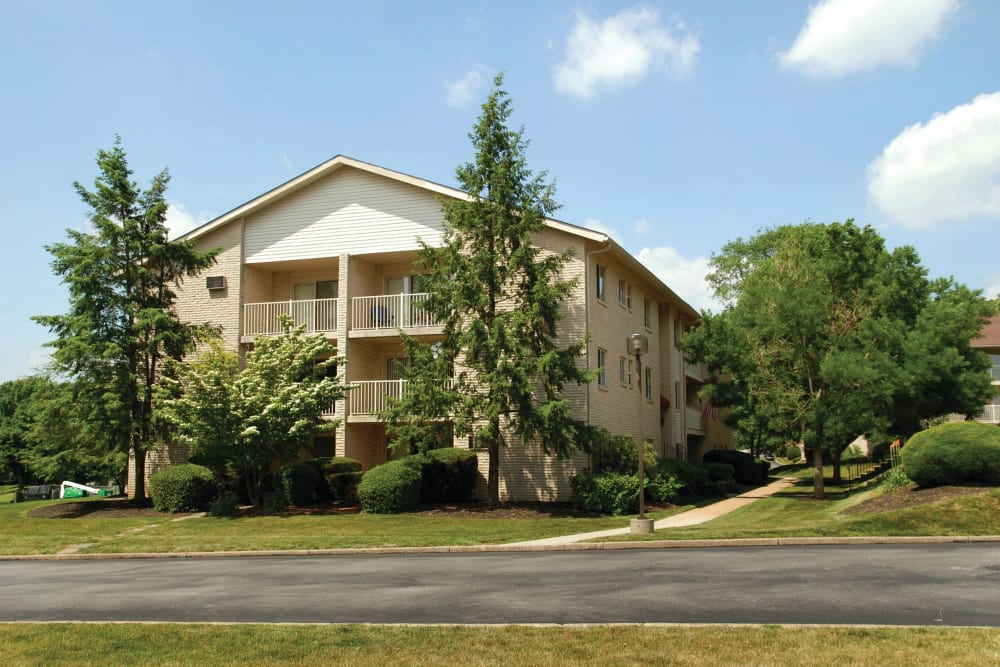 Apartment building lined by mature trees at Frazer Crossing in Malvern, Pennsylvania