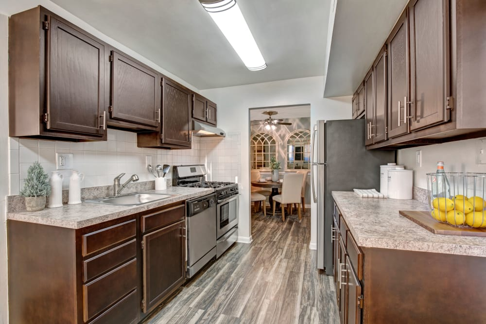Model kitchen with hardwood floors, dark wood cabinets and granite countertops at The Gateway in Gaithersburg, Maryland