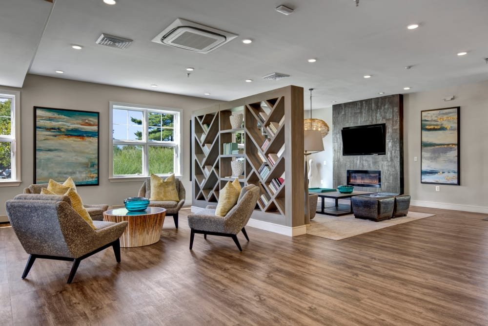 Large open living room with accent chairs surrounding a coffee table and modern artwork at The Gateway in Gaithersburg, Maryland