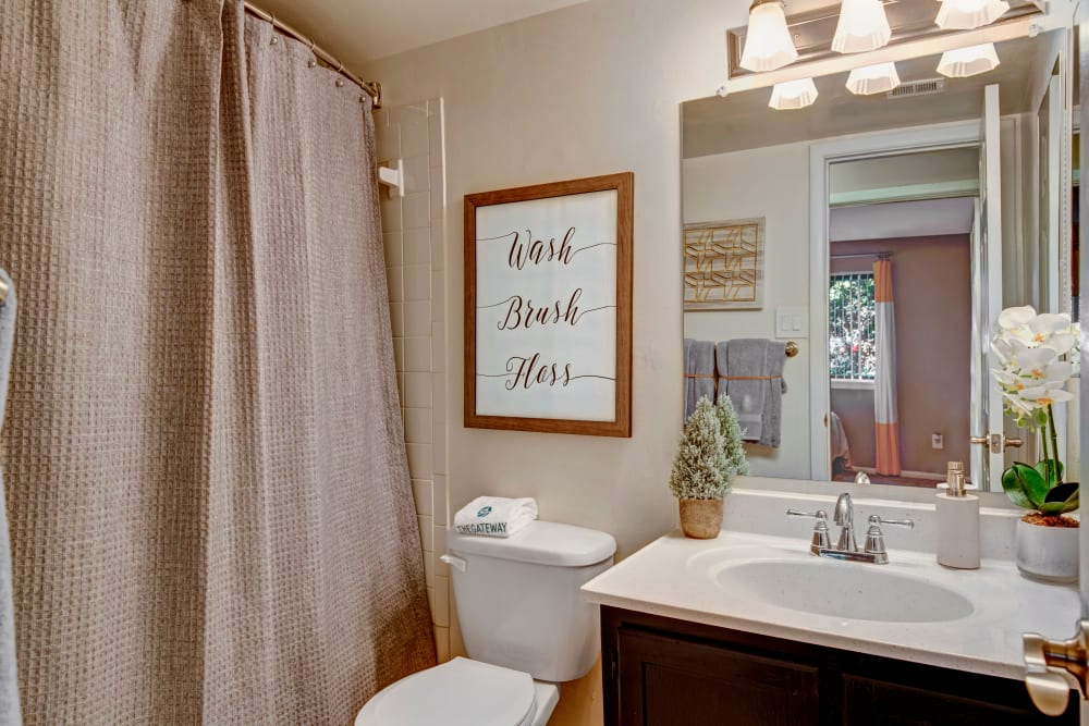 Model bathroom with large vanity mirror and oval tub at The Gateway in Gaithersburg, Maryland