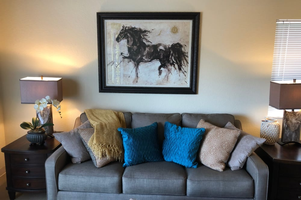 A couch and wall art in a resident apartment at The Lakes at Banning in Banning, California.