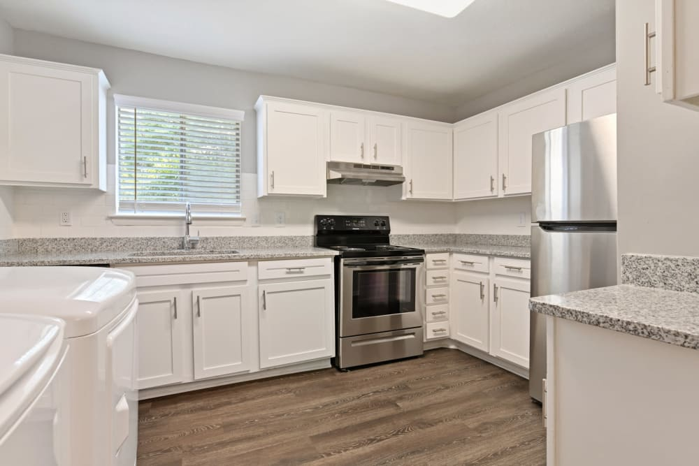 Large kitchen with bright white cabinetry and hardwood-style flooring in a model apartment at Crest at Riverside in Roswell, Georgia