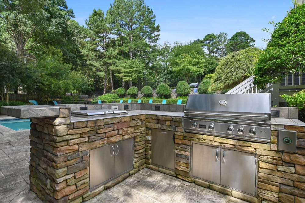 Gas grills at the barbecue area with a view of the pool at Crest at Riverside in Roswell, Georgia