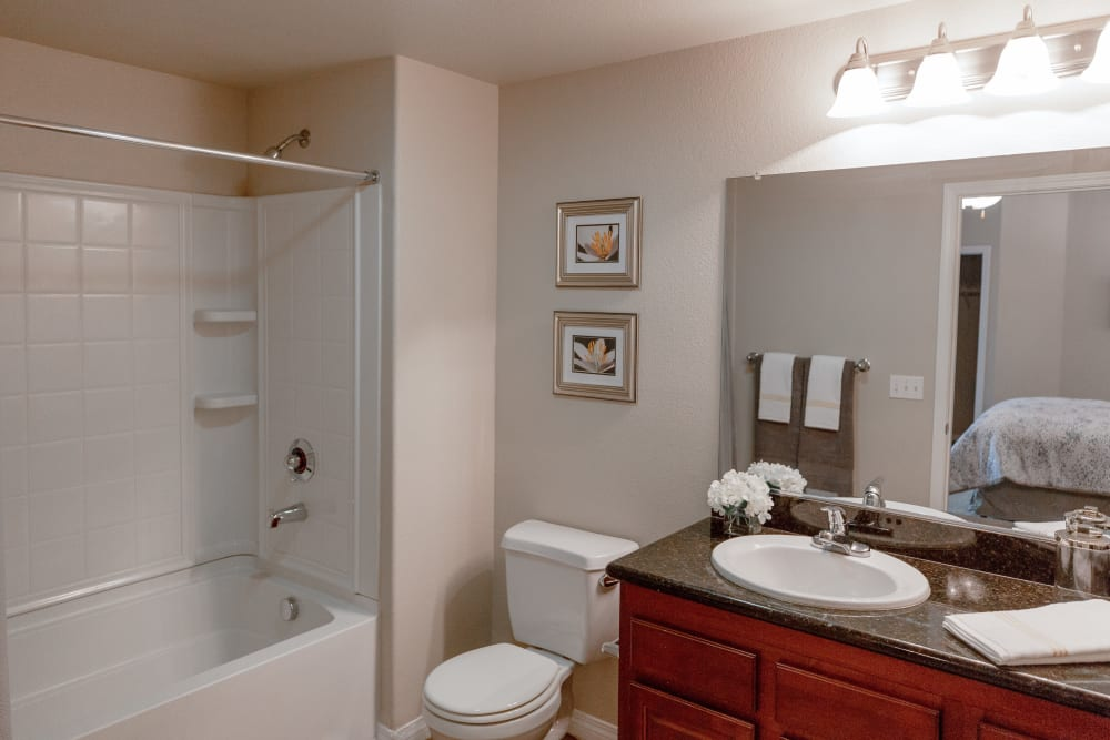 Bathroom with a large vanity mirror at Wolf Ranch Condominium Rentals in Sacramento, California