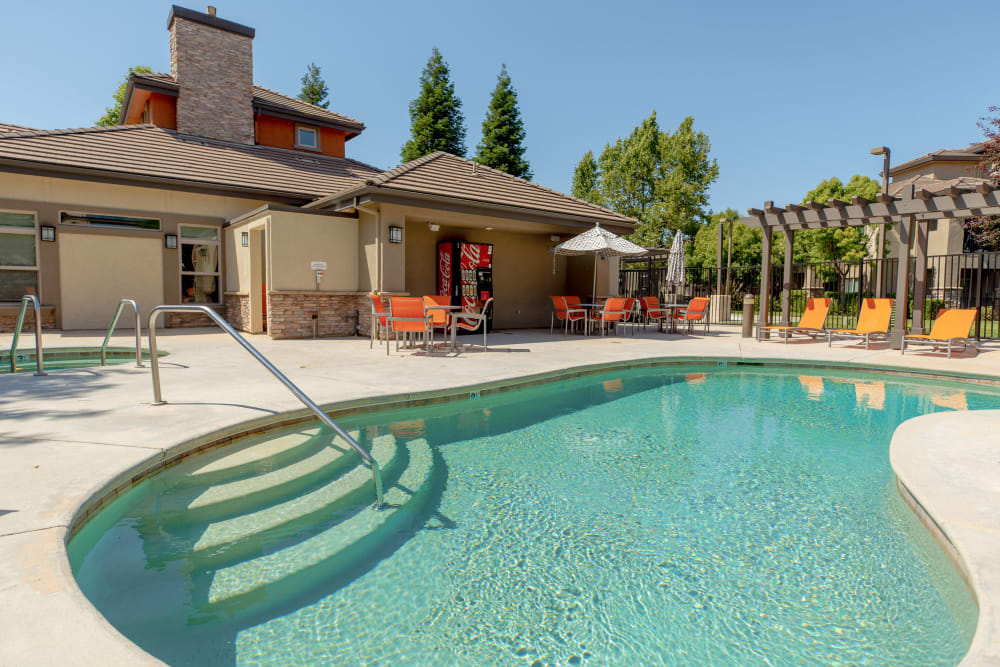 Outdoor swimming pool with lounge chairs at Wolf Ranch Condominium Rentals in Sacramento, California