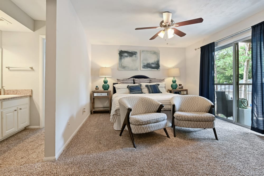 Primary bedroom with a ceiling fan and a draped sliding door leading to the private balcony outside a model home at Crest at Riverside in Roswell, Georgia