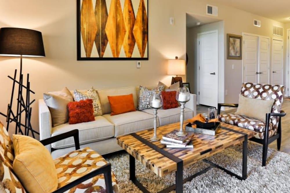 Living room with white couch and stylish chairs in an apartment at Luxe Scottsdale Apartments in Scottsdale, Arizona