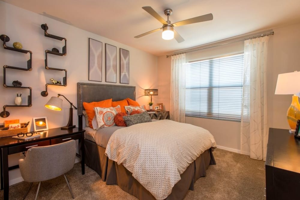 Bedroom featuring interesting art on the walls and ceiling fan to help keep it cool at Luxe Scottsdale Apartments in Scottsdale, Arizona