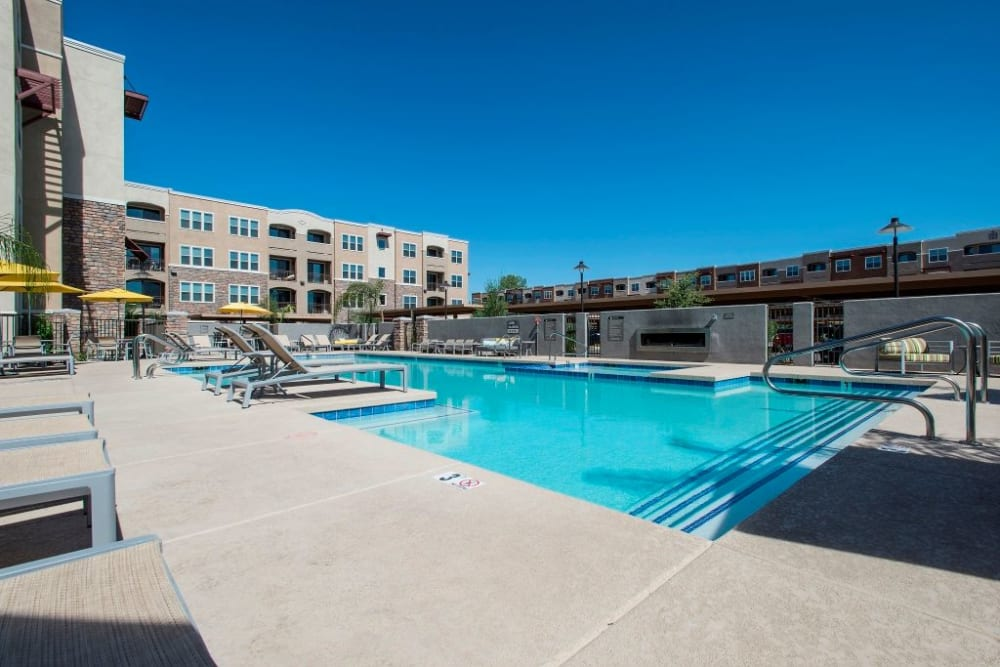 Community pool with apartment buildings in the background at Luxe Scottsdale Apartments in Scottsdale, Arizona