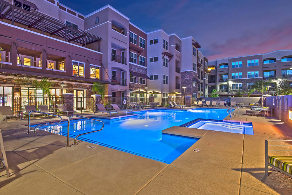 Apartment buildings and community pool lit up at night at Luxe Scottsdale Apartments in Scottsdale, Arizona