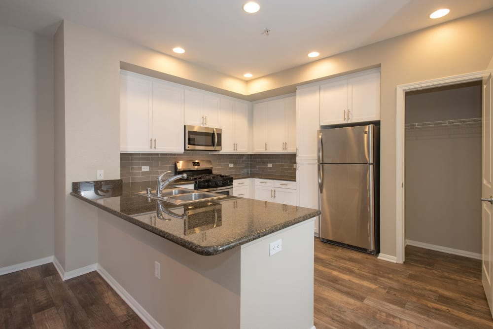 Gourmet kitchen with stainless-steel appliances looking into the living space of a model home at Paragon at Old Town in Monrovia, California