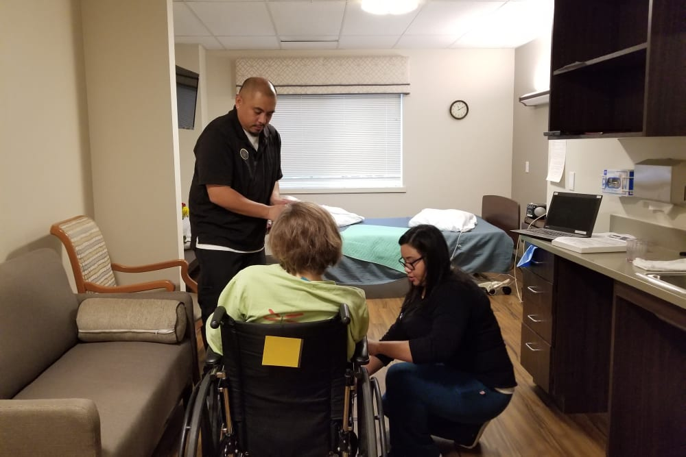 Staff members help a resident into their room at Mission Healthcare at Bellevue in Bellevue, Washington.