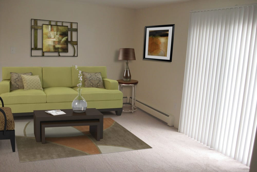 Living room with bright green velvet couch at The Village at Marshfield in Marshfield, Massachusetts