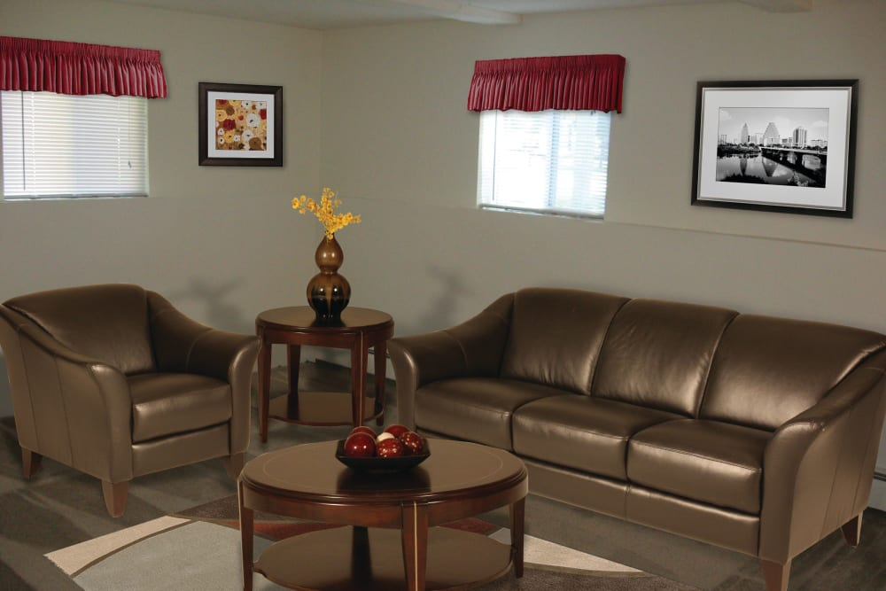 Living room with leather couches at The Village at Marshfield in Marshfield, Massachusetts