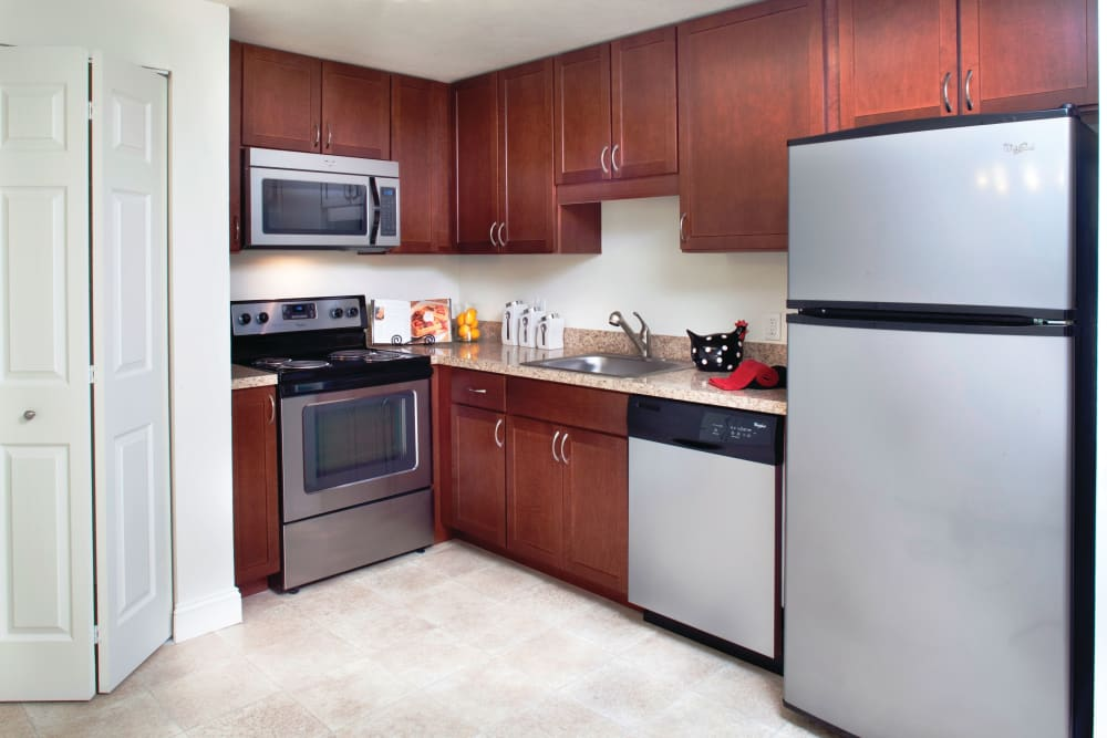 Kitchen with stainless steel appliances and cherry wood cabinets at The Village at Marshfield in Marshfield, Massachusetts