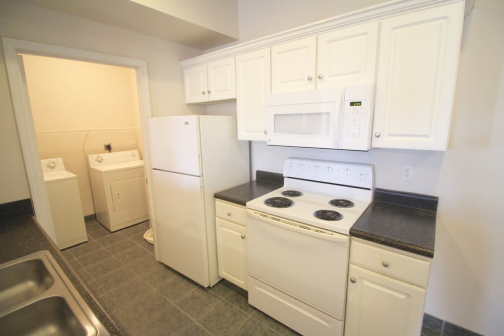 Kitchen with a view of the washer and dryer room at Timber Lakes Apartment Homes in Kansas City, Missouri
