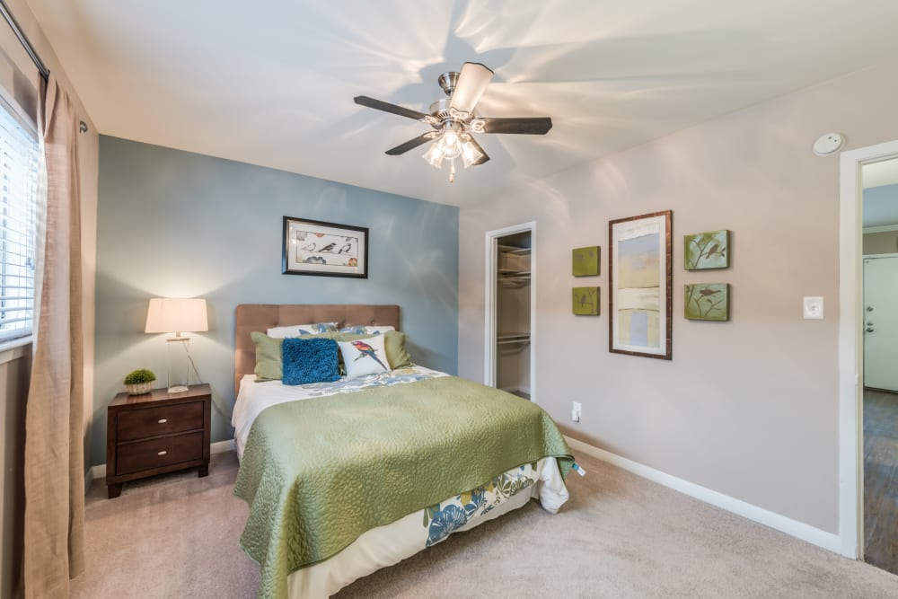 Well decorated model bedroom with ceiling fan at The Villages at Meyerland in Houston, Texas