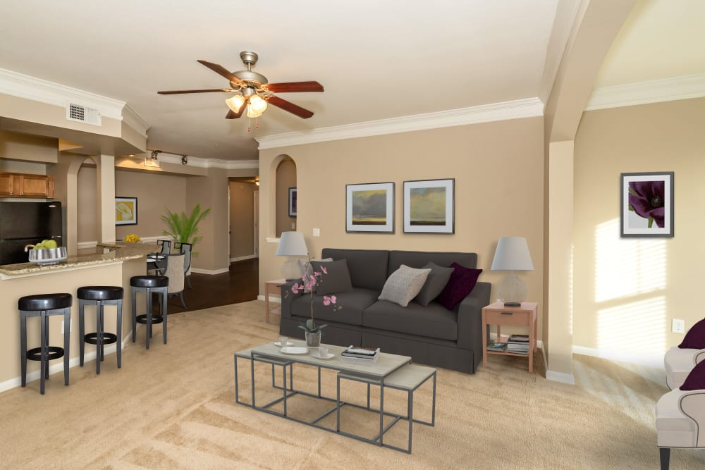 Model living room with a view of the kitchen bar at Vista 121 Apartment Homes in Lewisville, Texas