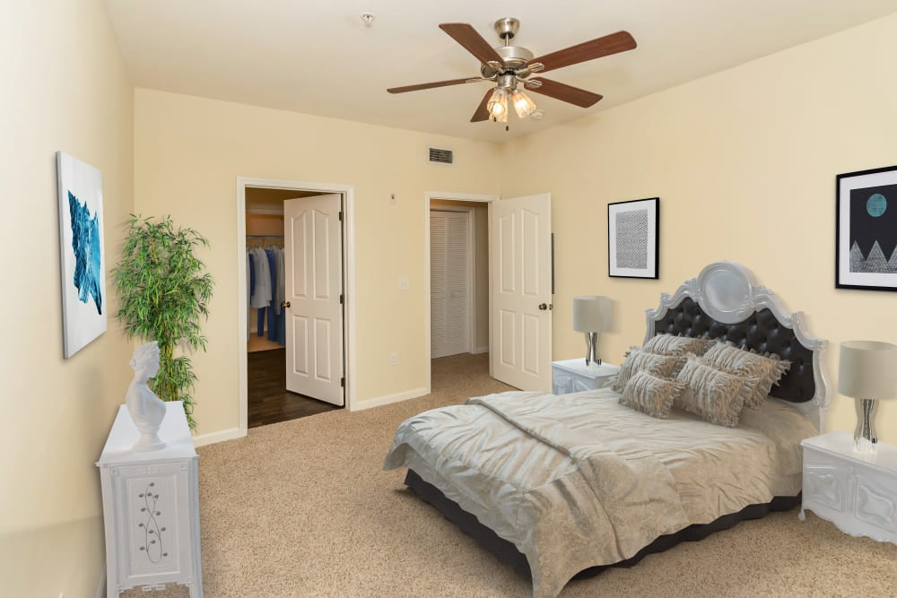 Brightly lit model bedroom with ceiling fan at Vista 121 Apartment Homes in Lewisville, Texas