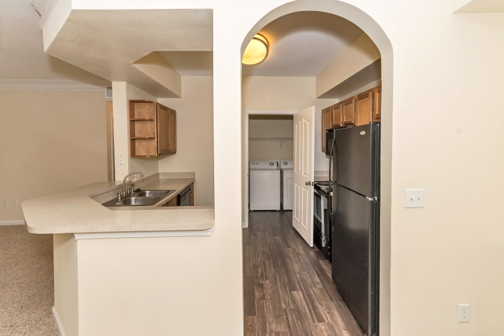 Side view of the kitchen and kitchen bar at Vista 121 Apartment Homes in Lewisville, Texas