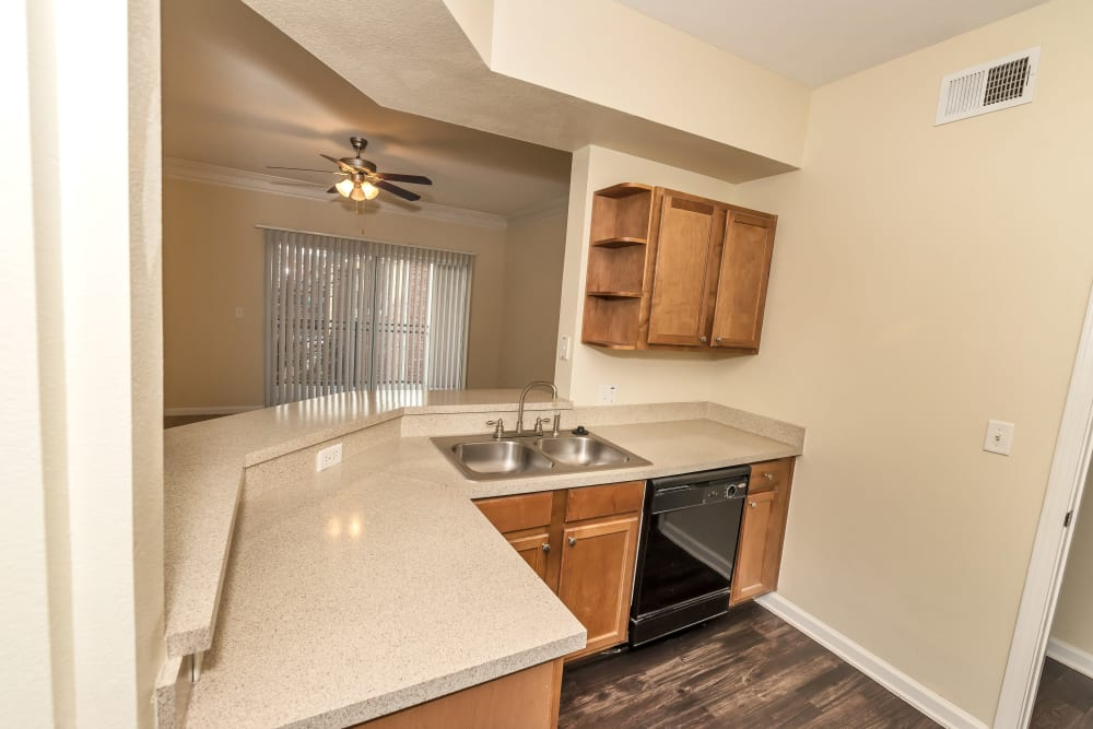 Model kitchen with granite countertops and stainless steel appliances at Vista 121 Apartment Homes in Lewisville, Texas
