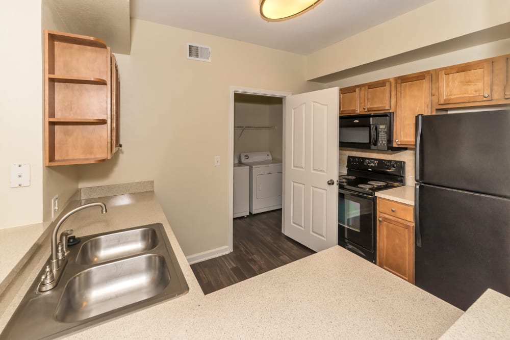 Model kitchen with a view of the in unit washer and dryer room at Vista 121 Apartment Homes in Lewisville, Texas