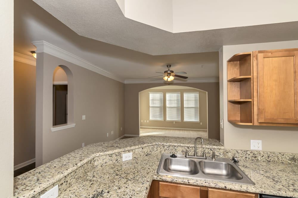 Kitchen bar overlooking empty model living room at Vista 121 Apartment Homes in Lewisville, Texas