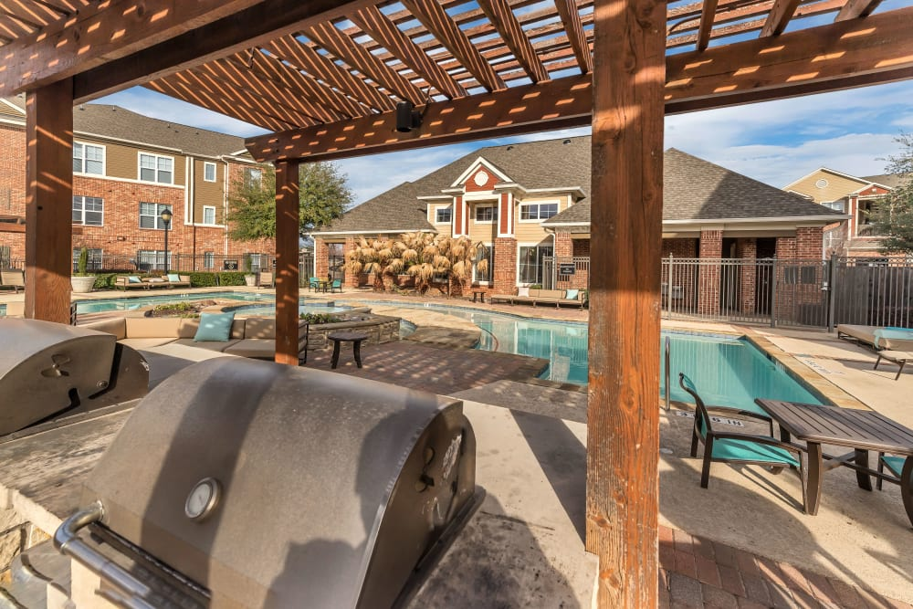 Outdoor barbecue poolside at Vista 121 Apartment Homes in Lewisville, Texas