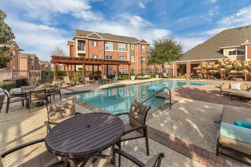 Shaded tables and seating poolside at Vista 121 Apartment Homes in Lewisville, Texas