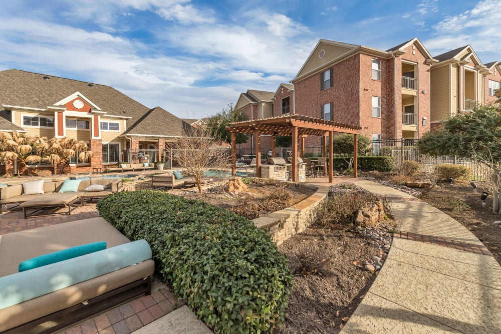 Outdoor couches poolside at Vista 121 Apartment Homes in Lewisville, Texas