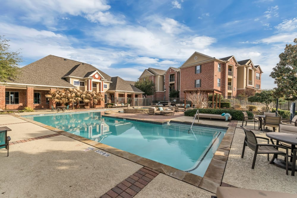View of the clubhouse from the pool at Vista 121 Apartment Homes in Lewisville, Texas