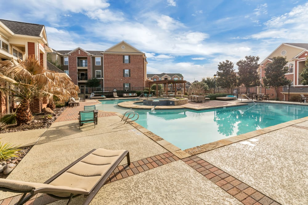 Sunny lounge chairs poolside at Vista 121 Apartment Homes in Lewisville, Texas