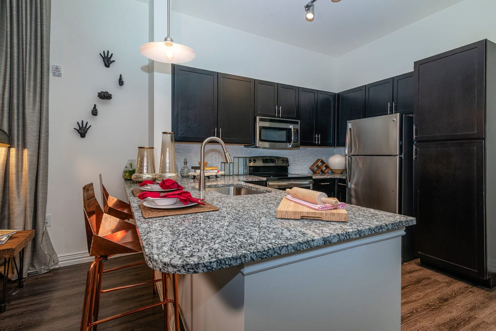 Granite countertops in a model home's kitchen at Twin Creeks Crossing in Allen, Texas