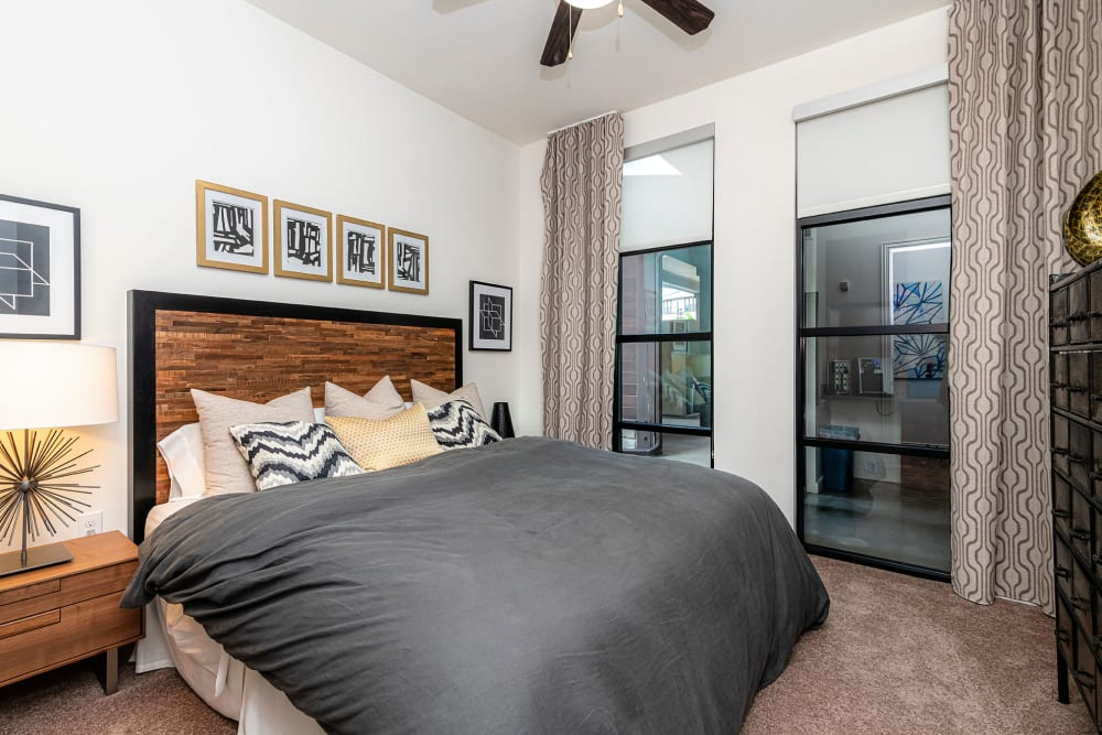 Ceiling fan and modern furnishings in the primary bedroom of a contemporary model home at Twin Creeks Crossing in Allen, Texas