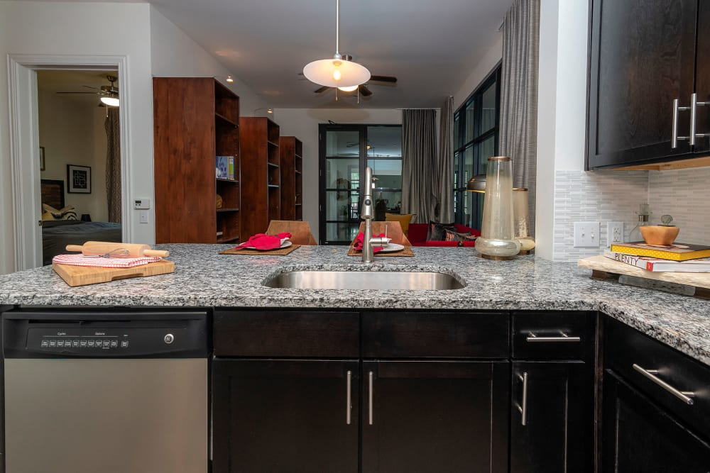 Gourmet kitchen with a view of the living area in a contemporary model home at Twin Creeks Crossing in Allen, Texas
