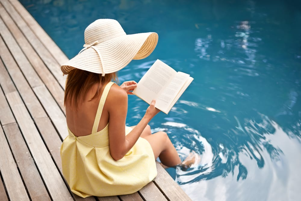 A resident reading a book with her feet in the pool at Artisan Living Bella Citta in Davenport, Florida