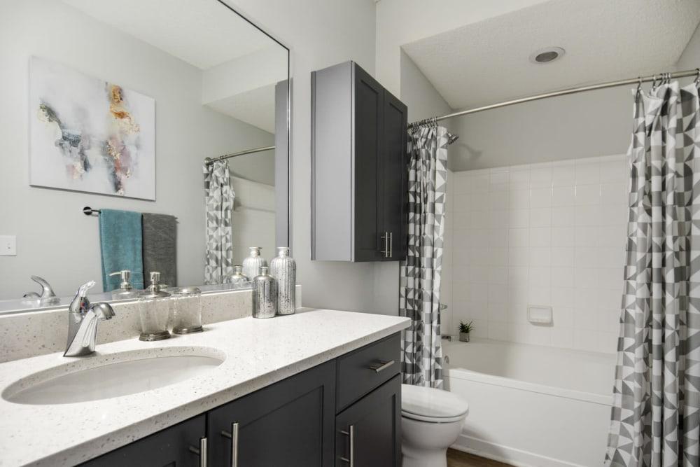 Quartz countertop and a large vanity mirror in a model apartment's bathroom at Ellington Midtown in Atlanta, Georgia
