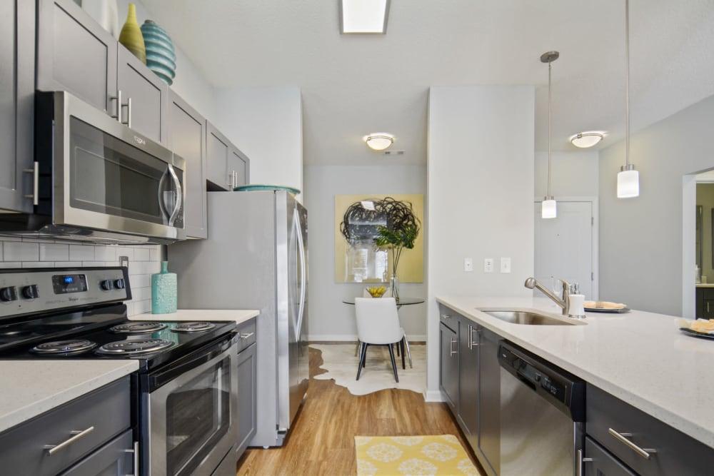 Stainless-steel appliances and quartz countertops in a model apartment's kitchen at Ellington Midtown in Atlanta, Georgia