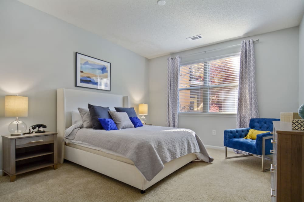 Plush carpeting and a large draped bay window in the primary bedroom of a model home at Ellington Midtown in Atlanta, Georgia