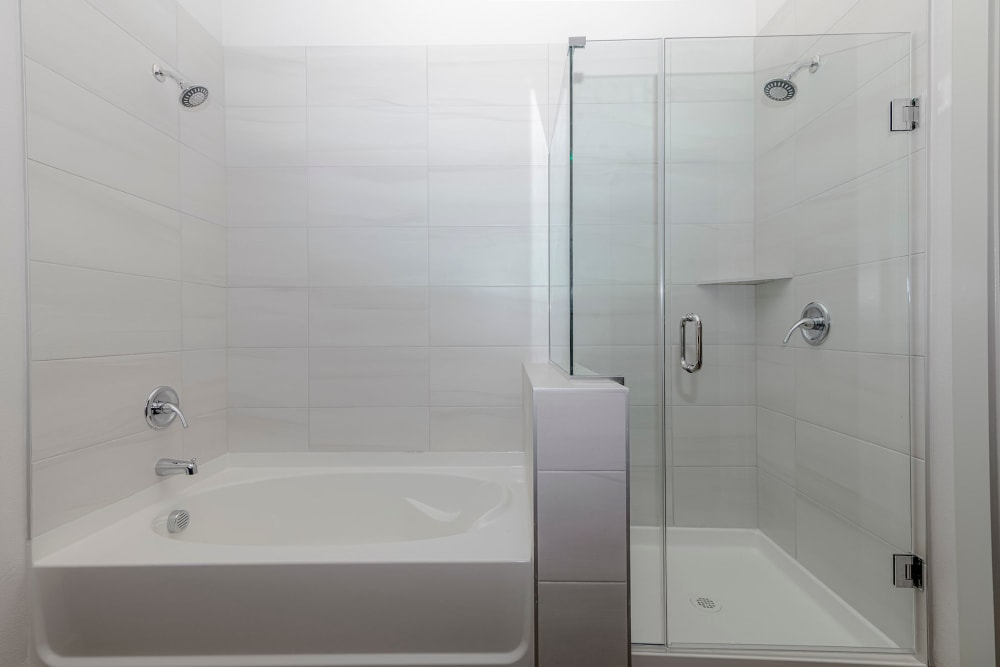 Bathtub and stand-up shower with glass door in a model home's bathroom at Magnolia on the Green in Allen, Texas