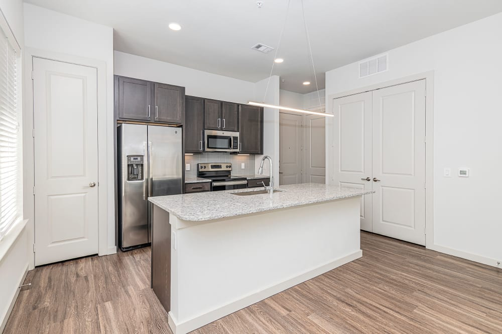 Granite countertops and stainless-steel appliances in a model home's kitchen at Magnolia on the Green in Allen, Texas
