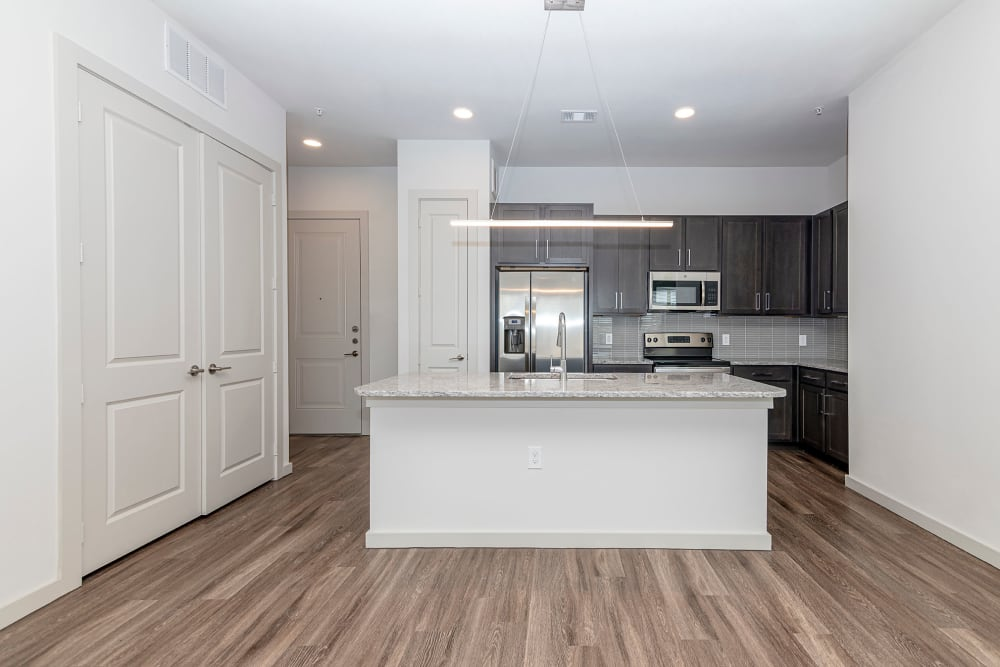 View of the modern kitchen over the breakfast bar of a model home at Magnolia on the Green in Allen, Texas