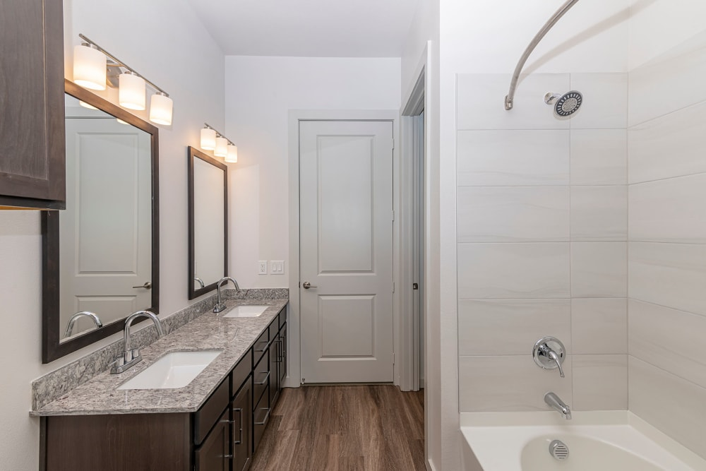 Dual sinks and vanity mirrors in the primary bathroom of a model home at Magnolia on the Green in Allen, Texas
