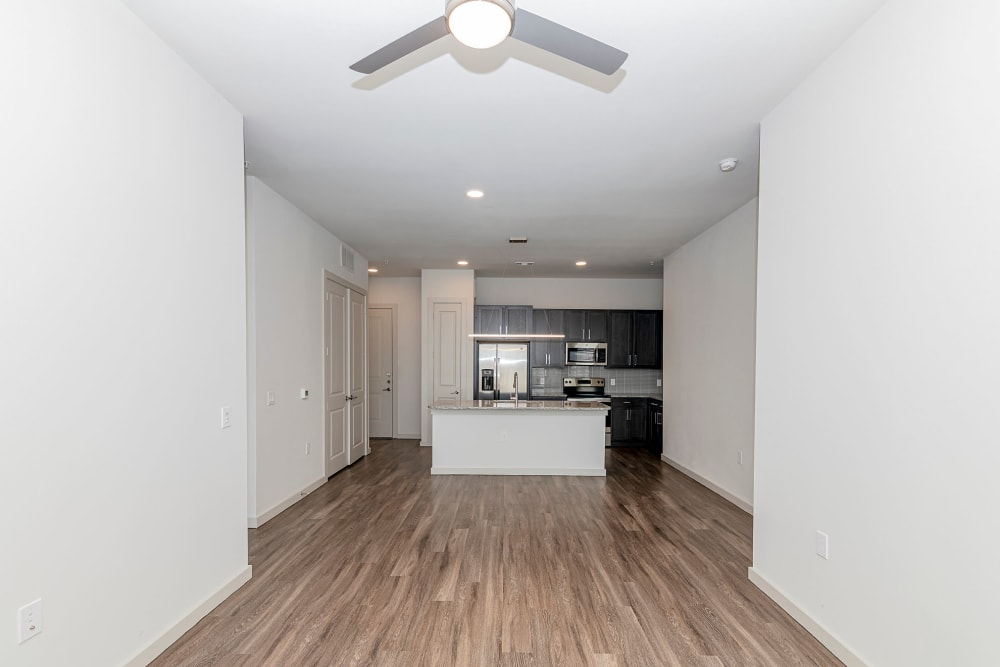 Spacious open-concept floor plan with a ceiling fan and hardwood flooring in a model apartment at Magnolia on the Green in Allen, Texas
