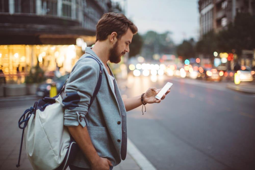 Resident checking his phone at a stoplight downtown while walking to work near Ellington Midtown in Atlanta, Georgia