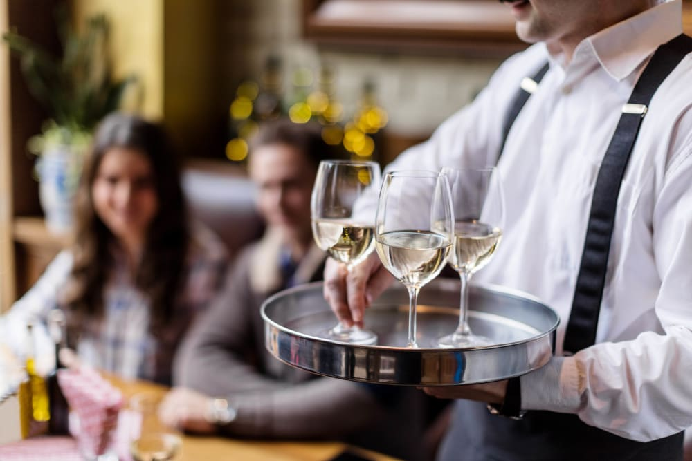 Server delivering glasses of wine to a group of resident friends at a restaurant near Ellington Midtown in Atlanta, Georgia