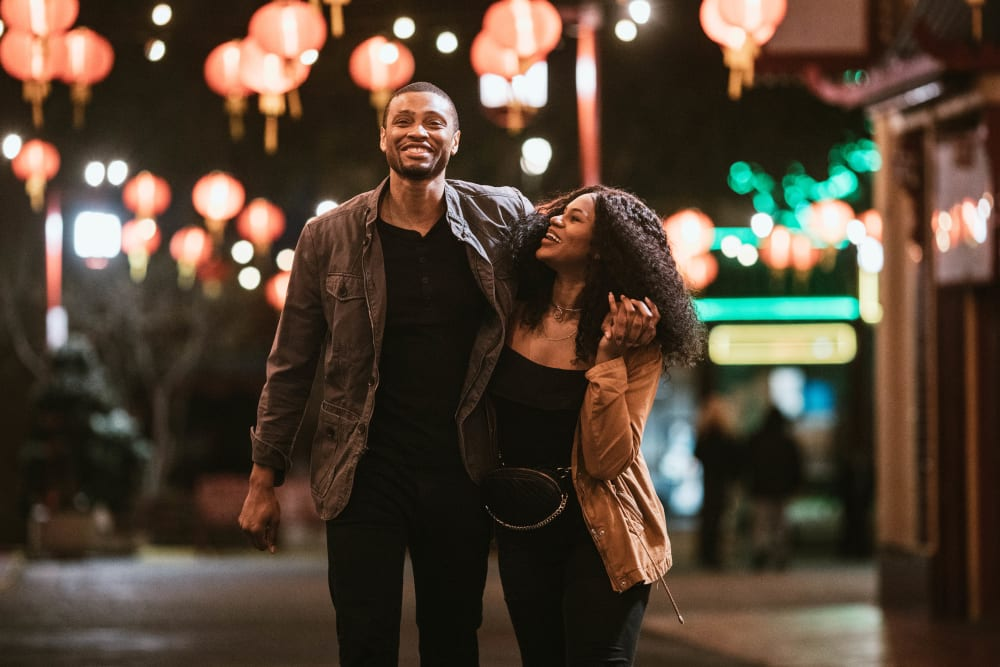 Couple with their arms around each other while walking downtown in the evening near Ellington Midtown in Atlanta, Georgia