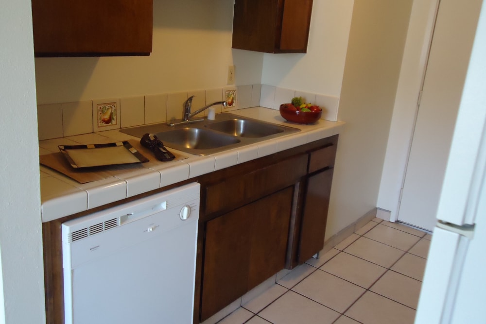 Kitchen unit with tile floor at Olympus Court Apartments in Bakersfield, California
